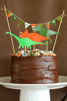 LOVE this simple chocolate cake with the candy rocks and dino cut outs - I think I'd go without the banner - love everything else.  Could also use large plastic dinos