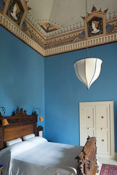 A Mediterranean-blue guest room with a 19th-century bed carved with the Guarini coat of arms (Photo: Ricardo Labougle)