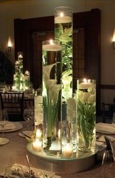 The table centerpieces will be tall vases at varying heights filled with submerged white calla lilies, white roses and white tulips with floating candles on top. Gorgeous for wedding centerpiece