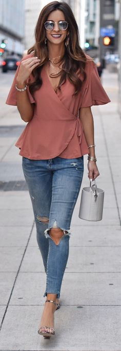 #spring #outfits woman in blue jeans holding bag while walking. Pic by @myviewinheels