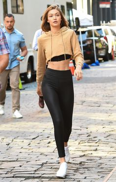 Fall Outfit Ideas: What to Wear With Leggings - Gigi Hadid in a camel cropped hoodie, high-waisted black leggings and white sneakers