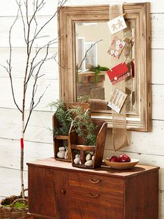 Clothespins hold holiday cards on burlap ribbon tacked to the back of a mirror frame. Cut tree in a basket. Wrapped trunk with yarn