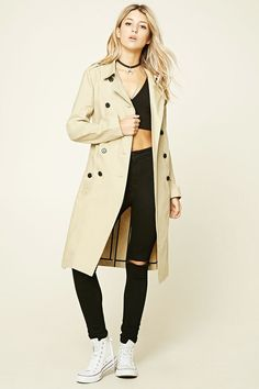 A woven trench coat featuring an included belt, basic collar, a double breasted button front, two front slit pockets, long sleeves, and a longline silhouette.