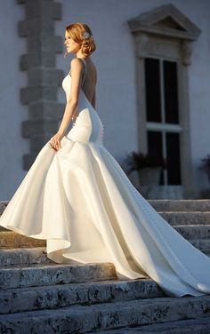 """An impressive 600"""" hemline, fabric-covered buttons, and Swarovski crystal straps complete the look of this modern fit-and-flare wedding dress from Martina Liana."""