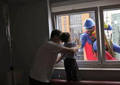 m homem vestido de Superman sorri para o pequeno João Bertola,  que está internado em um hospital em São Paulo.
