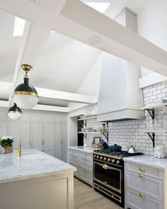 Illuminated by skylights fitted to a sloped ceiling, this gorgeous gray and white kitchen boasts a white hood mounted to white subway backsplash tiles accented with black grout above a La Cornue CornuFe Range and between iron and marble shelves.