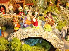 Les danseurs sont accompagnés par des musiciens installés sur le pont. De gauche à droite nous apercevons la femme tambourinaire du santonnier Richard d'Aix, celle d'Escoffier, de Carbonel et la femme tambourinaire de Truffiertout à fait à droite sur le pont.