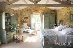 Distressed wood surfaces, regional yellow pottery, and accessories such as a wild boar tavern sign reflect the architecture's rustic style. The contrast of a fancy trumeau against a wall only heightens the rough and humble feel of the place. Antique painted furniture complements the master bedroom's rustic architecture. Bed linens and matelassé coverlet, the White Company. French 18th-century toile de Jouy quilt. Swedish 18th-century secretary. French 18th-century armoire.