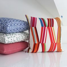 Have fun with your pillow pattern mixing!  In this example, the lead fabric has large multi-colored diamond shapes. The other pillows are various smaller patterns, each a slightly different scale, and each in a different color that plays off the lead fabric.  In addition, two of the four pillows have a light background, and two have colored backgrounds, which helps to break things up a bit.  The result is a fresh and exciting mix. Shop these and other designer pillow covers at Stuck on Hue!