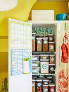 Calendars and chore lists hidden on the inside of the doors of a pantry that is organized with labeled containers.