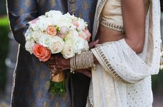 Ivory rose wedding bouquet with coral and gold accents.