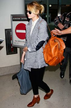 Emma Stone showed off her ever-stylish off-duty wardrobe pairing her chic tweed jacket with tan accessories and retro Ray Bans
