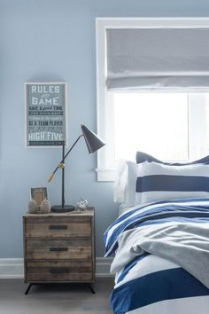 Blue and gray boy's bedroom features a wall painted blue framing a window dressed in a gray roman shade placed over a bed dressed in white and blue awning striped duvet and shams placed next to a plank 3 drawer wood nightstand and a black and gold task lamp.