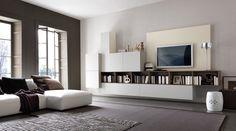 Esto es el cuarto de estar, donde hay un sofá, una televisión, muchas estanterías con varios libros,una lámpara,dos luminosas ventanas y dos alfombras de rayas.  Perfecto para mirar películas y descansarse!