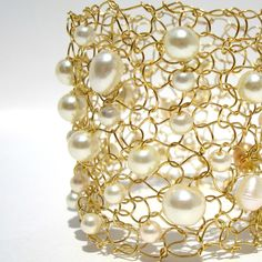 The hand knit gold toned wire cuff is absolutely striking, yet delicate at the same time. This cuff is open and artistic and has different shapes and sizes of ivory cream freshwater and glass pearls floating throughout the bracelet. MEMBER - lapisbeach