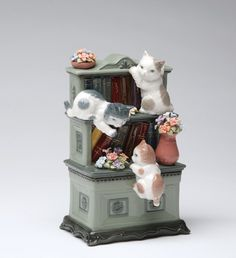 These three playful kittens are climbing all over this ornate little green bookcase. Three bouquets of miniature hand rolled porcelain flowers adorn this musical.
