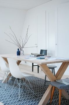We now change the theme and we analyze a home office. As you can see, the décor is very simple, austere even. The work table is made of wood with a natural finish and it's surrounded by various types of chairs, among which two white Eames side chairs.