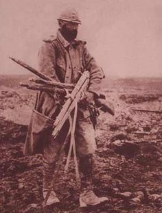 WW1. This rare photo shows a French Poilu tasked with the recovery of enemy war material from the battlefield following a successful advance, in this case carrying an armload full of five Gew 88s. gunsmagazine.com