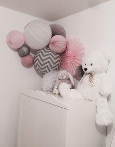 Cette belle combinaison de lampions gris et rose créé une ambiance douce et originale dans la chambre de Maëlya. Si vous choisissez des murs et des meubles blancs, une composition permet d'ajouter de la couleur et un peu de pep's comme dans cette cette jolie déco !