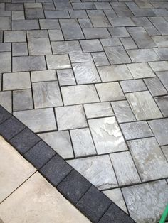 Beautiful patio using Unilock brick pavers. Stonehenge coping, Series 3000 black accent brick and Richcliff dawnwood patio pavers.