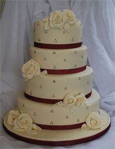 Beautiful designs - elegant and chic. Four tier ivory wedding cake with red ribbon trim, white sugar roses and subtle dotted detailing