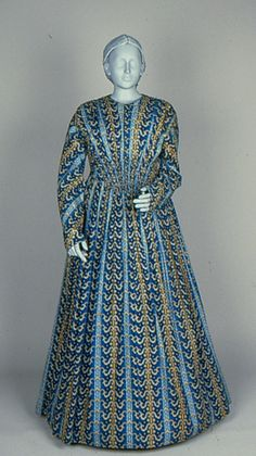 Dress Accession Number: 1999.50.1 Place Made: USA Date Made: 1845-1848 Description: Dress; printed cotton, ombre stripes with overprinted scrolls in blues and browns, long sleeves. Fabric is ombre print in shades of blue, with beige, yellow, brown, and white.