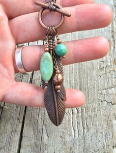 "Long, adjustable feather and turquoise copper necklace. This necklace may be worn long (32"") or doubled with a toggle clasp (16""). Pendant is made with antiqued copper, turquoise, turquoise magnesite."
