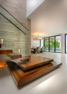 Floating wood stairs paired with a sleek glass railing lead the way to the modern home's second floor.                                                                                                                                                                                 More