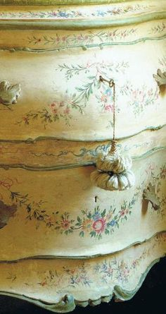 An antique French painted bombé chest in pale yellow decorated with multicolored floral garlands and finished with a passementerie tassel on the key.
