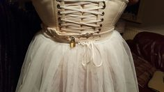 Locked in a corset with a very frilly hooped skirt