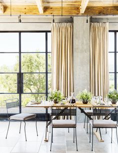 Elegant and timeless dining space in loft with centerpieces and tall curtains