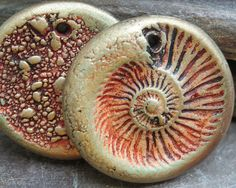 Polymer clay circle drops with ammonite pattern in rust and bronze.