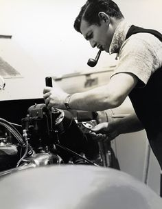 Clark Gable, working on a car and smoking a pipe