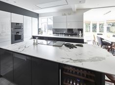 SieMatic S3 kitchen in Graphite Grey and Lotus White gloss finish, Dekton Aura and Quartz worktops, Gaggenau 200 series appliances, light stone flooring, smoked mirrored glass splashback, Farrow & Ball All White and Mole's Breath paint, Kartell Masters stool.  Bright, modern, classic kitchen. Kitchen inspiration, designed by Grid Thirteen Luxury Kitchens and Living. Leeds, West Yorkshire.
