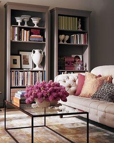 A pretty pink, peach & gray living room gets a custom look from a set of three painted bookcases