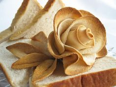 A lovely way to garnish a sandwich platter - single slice of flattened, then toasted bread fashioned to look like a blooming rose