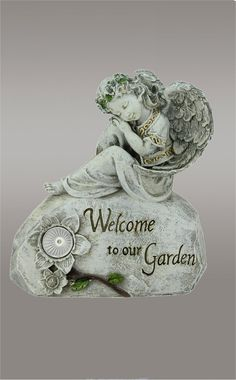 """Welcome To Our Garden"" Solar Powered Outdoor Patio Angel Statue Buy Solar Garden Angels Here!  This Cute Ange About 10"" High Is Solar Powered!  Glows A Charming White Light At Night.   Distressed Gray Finish With Soft Gold and Green Accents Flower. Order Online or Call:  1-800-417-9872 Today!"