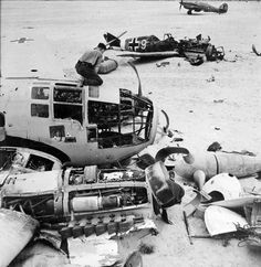 Allied ground crew disassembling a wrecked German He 111 aircraft near Daba and Fuka, Egypt, circa 1942; note wrecked Bf 109 fighter and Hur...