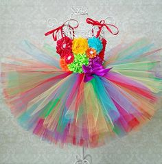 Rainbow Birthday Tutu Dress  This listing is for a Rainbow Flower Girl/Birthday Tutu Dress that is simply stunning. Made with every shade of the rainbow. Bodice is adorned with multiple styles of rainbow colored flowers.  Comes with red satin straps that ties over the shoulders in a pretty bow.  #rainbowdress #hungrycaterpillar #1stbirthday #rainbow #birthdaydress #birthdayoutfit #birthdaytutu #tutu #tutudress #rainbowoutfit #pageantdress #cakesmash #cakesmashtutu #cakesmashdress