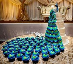 a wedding backdrop with a sugar peacock on top and matching cupcakes that form i. a wedding backdrop with a sugar peacock on top and matching cupcakes that form its tail. Peacock Cupcakes, Peacock Cake, Peacock Wedding Cake, Peacock Decor, Peacock Party Ideas, Ideas Party, Peacock Wedding Decorations, Wedding Flowers, Yellow Wedding Cakes
