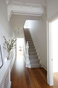 White staircase with wood floor and runner