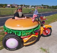 57-year-old Harry Sperl of Daytona Beach, Florida, has been collecting burger memorabilia for the past twenty-three years in order to turn his home into the world's first burger museum. Pictured here is his Hamburger Harley - a unique hamburger-shaped tricycle, with onion and tomato wheels, and pickle handles.