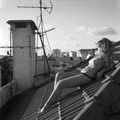 SASHA ALESSANDRO PANELLI Fotografia analogica ottenuta su medio formato, Lubitel 166+, pellicola BW. Stampata su carta fotografica, 40x40cm. 2013  Era un pomeriggio di nuvole rapide su Lisbona. Era troppo il vento oceanico per godersi la città, per colei che condivideva con me l'appartamento lisboeta decise di posare per me. Sfruttammo il tetto del nostro appartamento, sfidando le raffiche di aria ed il freddo di quel tramonto, che le causava una fotogenica pelle d'oca.