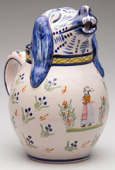 """FRENCH POTTERY HENRIOT QUIMPER OVOID PITCHER WITH AN APPLIED DOG'S HEAD IN HIGH RELIEF FORMED AS THE SPOUT, with applied c-form handle, painted with blue and yellow bands framing stylized florets in blue, green, purple and orange, the dog with a yellow collar, above a painted polychrome figure of a standing Breton woman between large flower sprays, unmarked. 20th Century. 9"""" H."""