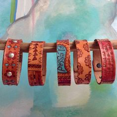 Each of these cuffs in drawn freehand with a pyrography tool onto vegetable tanned leather. I then add color (sometimes!) and finish each with a protective coating.  Over time, your bracelet will darken and become soft and supple. This is a characteristic of veg tan leather as it absorbs oils ...