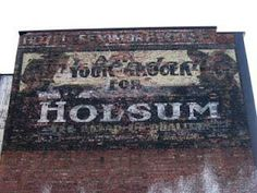"""This is what the sign looked like around 2008. It has now been defaced. It is an ad for Holsum.It reads """"Ask your Grocer for Holsum"""". I believe that is a brand of bread."""