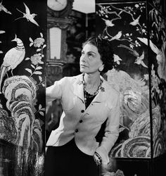 1937: Gabrielle Chanel in front of the Coromandel screens at 31 rue Cambon, Paris. Photographed by Lipnitzki. © Chanel / Lipnitzki/Roger-Viollet