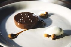 Chocolate Creameux - milk chocolate and vanilla crème filled with liquid salted caramel sitting on top of a hidden chocolate cookie. Sprinkled with sea salt and accompanied by hazelnuts and milk ice cream.
