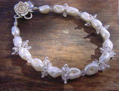 Natural freshwater pearls (not cultured) with tiny micro facet rose quartz charms and fastened with a silver rose clasp
