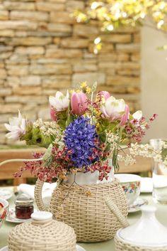 Sobre o centro da mesa, acomodamos os arranjos em trêsjarrinhas de porcelana branca trançadasna cor fendide tamanhos diferentes. Asjarrinhassão daColeção Petrópolise nelastambém podemos servir sucos, leite ou água.